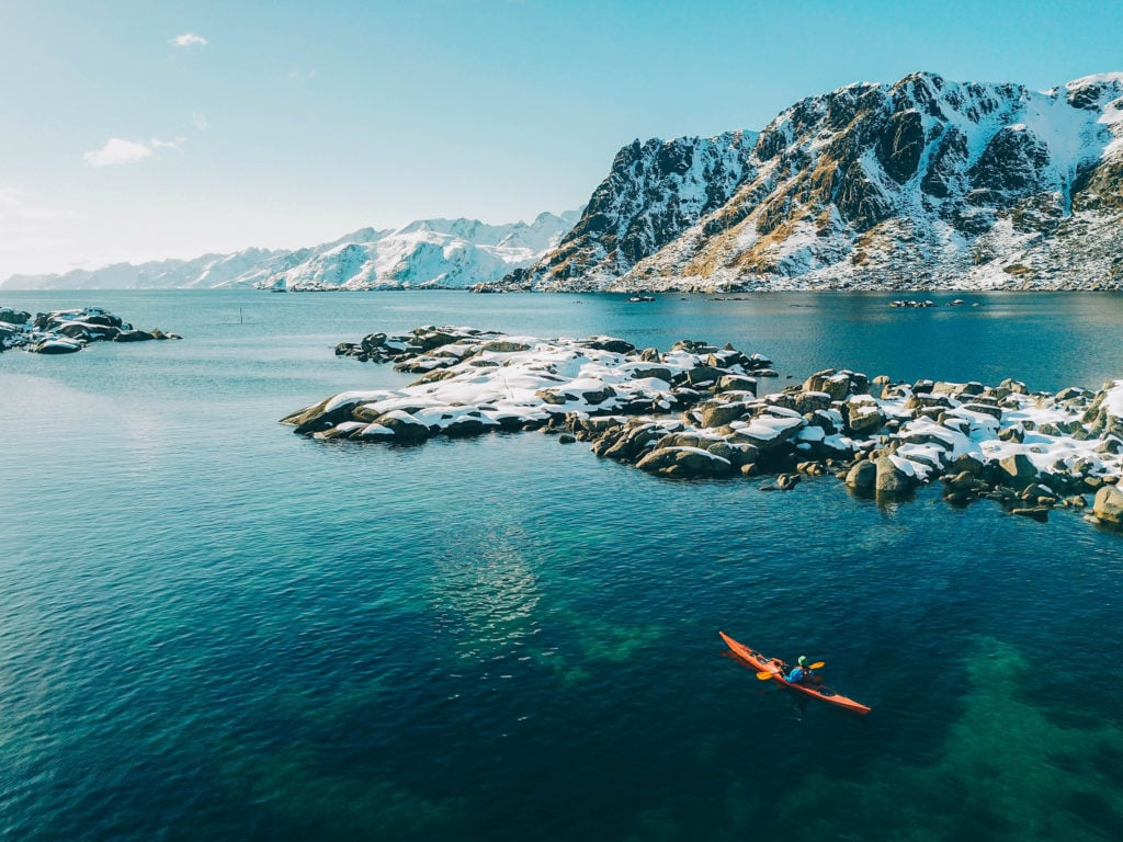 Sea kayak in lofoten with majestic mountains in the background.